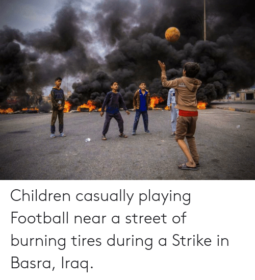 Children, Football, and Iraq: Children casually playing Football near a street of burning tires during a Strike in Basra, Iraq.