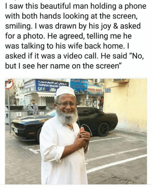 """Beautiful, Phone, and Saw: I saw this beautiful man holding a phone  with both hands looking at the screen,  smiling. I was drawn by his joy & asked  for a photo. He agreed, telling me he  was talking to his wife back home. I  asked if it was a video call. He said """"No,  but I see her name on the screen""""  DARWISH IBRAHIM"""