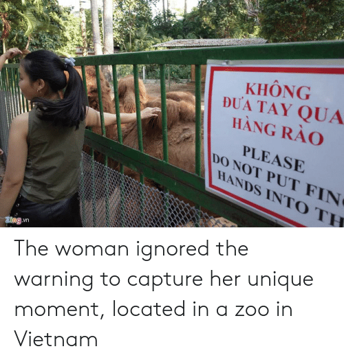 Vietnam, Her, and Zoo: KHONG  DUA TAY QUA  HANG RAO  PLEASE  DO NOT PUT FIN  HANDS INTO TH  9 The woman ignored the warning to capture her unique moment, located in a zoo in Vietnam