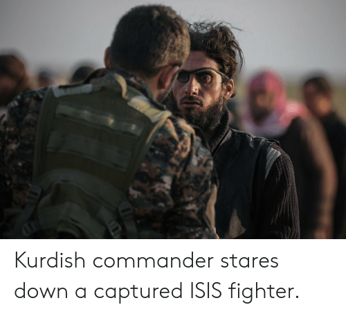 Isis, Kurdish, and Down: Kurdish commander stares down a captured ISIS fighter.