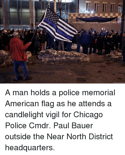 Chicago, Memes, and Police: NE  CHICAG  RTME A man holds a police memorial American flag as he attends a candlelight vigil for Chicago Police Cmdr. Paul Bauer outside the Near North District headquarters.