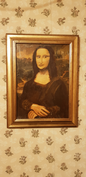 Mona Lisa looks like shes had a rough weekend. My colleague likes to paint and puts them in the toilets to scare/ impress us.: विसतत Mona Lisa looks like shes had a rough weekend. My colleague likes to paint and puts them in the toilets to scare/ impress us.