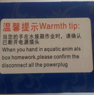 Aquarium, Text, and Water: |温馨提示Warmth tip:  当您的手在水族箱作业时, 请确认  已断开电源插头  When you hand in aquatic anim als  box homework, please confirm the  disconnect all the powerplug Text on the side of a box which contained aquarium water heater I ordered