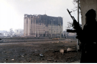 Dank, 🤖, and Palace: 耆  声 irTII A Chechen fighter near the burned-out ruins of the Presidential Palace in Grozny, January 1995.