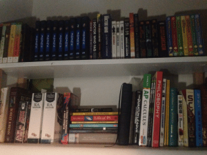 A view of my closet bookshelf.: 07  04  QLAYS  ARNOLD  THE  THE  LEGEND  OF DRIZZT  LEGEND  DRIZZT  ROBE  ANTRY  TOR  RA  RA  SALVATORE  SALVATORE  B0OK  O HOBBIT  OAN  RESISTING HAPPINESS  Life of Pi  Yann Martel  6 HICE ND AEN  JOHN STEINBECH  GAm Mata  ATHU  Beh of e S  MLER  RA SAL  Dip  SCOTT ITZCEDALD  Dip  THE COUNT  MONTE RISTO  WROT A  JOHN GREEN TH BUTP SIS  3s  SYTHE  NE-PUNCH WAIN  o 14Y  ts  CTOR  THE VISUAL IOTIORARY  E OFI  SARCASM  PHILOSOPHY  GRAVE  PERIL  I DOCTOR WHO VEN ooCTOR  INDOCTOR WHOBLVE DCTOR  PTER  BUTCHER  TITAN  RVEV  FOOL  MOD  71TAN  AP CALCULUS  BARRON'S  BUTCHER  STOR  FRON  THE  QUANTUM LEAGUE  HRWASEYEY  HARD PASL EVAMS  HADA  DOUGLAS ADAMS  THE SLENT SIARS O BY  BASTIFO CHADS  EARTHWORLD  DOCTOR WHO  12 00CTORS 12 STORIES  DOCTOR WHO FAQ  CHARACTER ENCYCLOPEDA  OsOs  THE STRANGE FASCINATIONS  OF NOAH HUPNOTIK  os  Otos  OS  Robort  Jordam THE GREAT  HUNT  nso  ROBERT JORDAN  Maay Wateis  AWi the Doot A view of my closet bookshelf.
