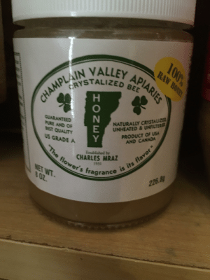 """Thanks I hate crystallized bees: 100%  RAW HONEY  CHAMPLAIN VALLEY APIARIES  NATURALLY CRYSTALIZE  UNHEATED & UNFILTER  PRODUCT OF USA  AND CANADA  GUARANTEED  PURE AND OF  BEST QUALITY  US GRADE A  """"The flower's fragrance is its flavor """"  Established by  CHARLES MRAZ  its flavor """"  1931  NET WT.  802.  226.8g  HONEY Thanks I hate crystallized bees"""