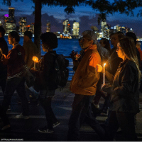 People carry lit candles along the Hudson River during a vigil and memorial march near the crime scene to remember the victims of the recent terror attack in New York City.: 13 1  AP Photo/Andres Kudacki) People carry lit candles along the Hudson River during a vigil and memorial march near the crime scene to remember the victims of the recent terror attack in New York City.