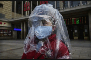 A boy covered in plastic to protect him from Coronavirus at a station in Beijing: A boy covered in plastic to protect him from Coronavirus at a station in Beijing