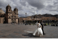 Memes, Peru, and 🤖: A bride and groom walk along at the Plaza de Armas in Cuzco, Peru, Saturday, Aug. 4, 2018.