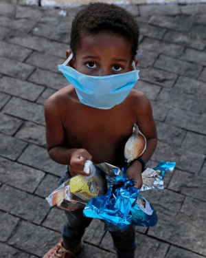 A child wearing a face mask receives food donations amidst the covid19 pandemic in Brazil: A child wearing a face mask receives food donations amidst the covid19 pandemic in Brazil