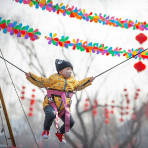 A child wore a face mask on an amusement ride in Beijing on Saturday.Credit:TNT: A child wore a face mask on an amusement ride in Beijing on Saturday.Credit:TNT