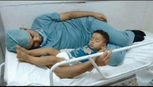 A doctor soothing a sick child to sleep ends up falling asleep himself: A doctor soothing a sick child to sleep ends up falling asleep himself