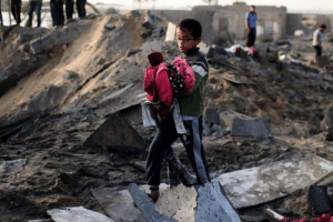 A kid retrieves clothes from his destroyed family home in Gaza.: A kid retrieves clothes from his destroyed family home in Gaza.