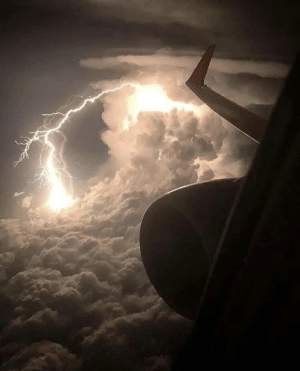 Lightning, Passenger, and Storm: A lightning storm seen from the window of a passenger plane at cruising altitude