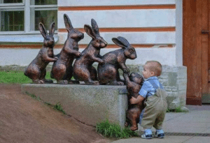A little kid helping a bunny statue: A little kid helping a bunny statue