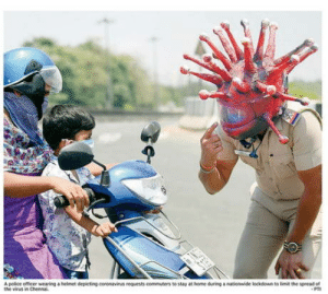 A police officer in India wearing a helmet depicting Coronavirus to stay at home.: A police officer in India wearing a helmet depicting Coronavirus to stay at home.