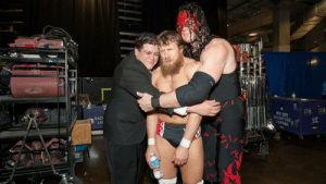 Ricardo Rodriguez and Kane hugging a reluctant Daniel Bryan backstage: ACKSTAGE  LIGHTING  BAC  LIC Ricardo Rodriguez and Kane hugging a reluctant Daniel Bryan backstage