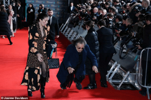Al Pacino tripping on the red carpet for the BAFTAs today whilst his girlfriend Meital Dohan looks on in terror: Al Pacino tripping on the red carpet for the BAFTAs today whilst his girlfriend Meital Dohan looks on in terror