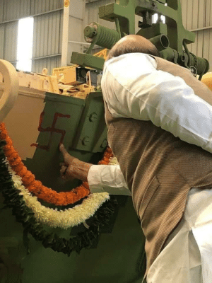 An Indian Minister drawing Swastika over newly acquired defense equipment. Swastika is a very important cultural symbol in most of South Asia .: An Indian Minister drawing Swastika over newly acquired defense equipment. Swastika is a very important cultural symbol in most of South Asia .