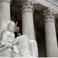 Memes, Protest, and Supreme: AP Photo/Alex Brandon Jessica Campbell-Swanson, from Denver, sits in the lap of the Contemplation of Justice statue as activists protest on the steps of the Supreme Court after the confirmation vote of Brett Kavanaugh, on Capitol Hill Saturday.