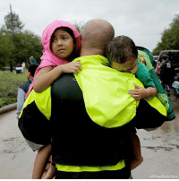 A police officer carries a brother and sister to dry ground after their neighborhood was inundated with water from Tropical Storm Harvey.: AP Photo/Charlie Riedel A police officer carries a brother and sister to dry ground after their neighborhood was inundated with water from Tropical Storm Harvey.