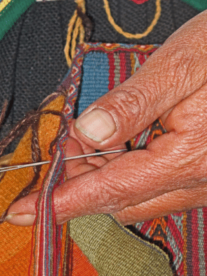 Artisan adding edge to a blanket in a collective in Peru.: Artisan adding edge to a blanket in a collective in Peru.