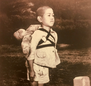 As we joke about WWIII here is a pic of a Japanese boy waiting in line at the crematorium with his deceased baby brother on his back, Nagasaki, 1945.: As we joke about WWIII here is a pic of a Japanese boy waiting in line at the crematorium with his deceased baby brother on his back, Nagasaki, 1945.