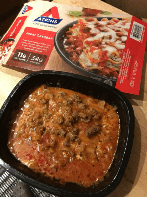 Lasagna, Living, and Reality: ATKINS  LOW CARB LIVING  Meat Lasagna  Three layer lasagna  ricotta chees  filled with  topped wit  & meat sauce and  tomato  mozzarella cheese  11G 34G  NETCARBSPROTEIN  GSUGGESTION  U.S Expectations VS Reality - Atkins really setting the bar in terms of quality microwave meals