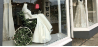 Chair, Mannequin, and  Wheel: BE A bridal boutique put a mannequin in a wheel chair