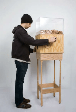 bencrowther:  This machine allows anyone to work for minimum wage for as long as they like. Turning the crank on the side releases one penny every 4.97 seconds, for a total of $7.25 per hour. This corresponds to minimum wage for a person in New York. This piece is brilliant on multiple levels, particularly as social commentary. Without a doubt, most people who started operating the machine for fun would quicklygrow disheartened and stop when realizing just how little they're earning by turning this mindless crank. A person would then conceivably realize that this is what nearly two million people in the United States do every day…at much harder jobs than turning a crank. This turns the piece into a simple, yet effective argument for raising the minimum wage. : bencrowther:  This machine allows anyone to work for minimum wage for as long as they like. Turning the crank on the side releases one penny every 4.97 seconds, for a total of $7.25 per hour. This corresponds to minimum wage for a person in New York. This piece is brilliant on multiple levels, particularly as social commentary. Without a doubt, most people who started operating the machine for fun would quicklygrow disheartened and stop when realizing just how little they're earning by turning this mindless crank. A person would then conceivably realize that this is what nearly two million people in the United States do every day…at much harder jobs than turning a crank. This turns the piece into a simple, yet effective argument for raising the minimum wage.