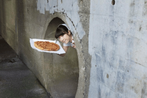 Casually holding a pizza in a sewer: Casually holding a pizza in a sewer