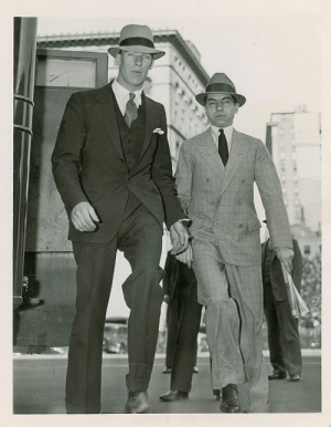 """The Office, Prison, and Office: Charles """"Lucky"""" Luciano handcuffed to a guard during prison transport. Two years before his deal with The Office Of Naval Intelligence in Operation Underworld against the Axis. (1940)"""
