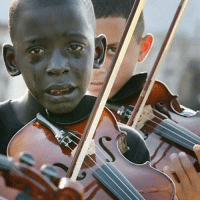 Child playing the violin at his teacher's funeral, who helped him escape poverty and violence through music.: Child playing the violin at his teacher's funeral, who helped him escape poverty and violence through music.