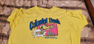 Maybe it's just me, but this 80s tee wants to crush special needs infant under its heel.: Colomial Bank  STOMP  OUT  BIRTH  DEFECTS  MARCH OF DIMES  Walk America Maybe it's just me, but this 80s tee wants to crush special needs infant under its heel.