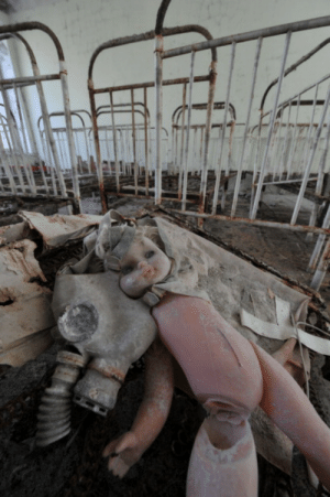 Tumblr, Blog, and Ghost: congenitaldisease:  A doll and a gas mask are pictured on a bed in one of the kindergarten of the ghost city of Pripyat on April 18, 2011. In the heart of Chernobyl, Ukrainian specialists regularly venture inside the concrete cover sheltering the ruined reactor after it exploded on April 26, 1986 to check its structure and radiation levels.