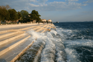 Target, Tumblr, and Waves: coolthingoftheday: The Sea Organ is an experimental musical instrument that is located in Zadar, Croatia. Beneath the white marble steps, a series of tubes create a system that could be described as a large piano. When the waves or the wind flow through the holes, they interact with the organ to create random harmonic sounds. (Source) You can listen to the sounds that the Sea Organ produces here.   Imagine in a sort of post apocalyptic world, the area is deserted, lots of ruins, and a mist is coming off the sea, and all you hear is this