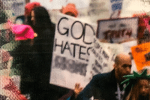 """Detail of a photo of the 2017 Women's March shown in the national archives. """"Trump"""" was blurred out (among other edits in the full image).: Detail of a photo of the 2017 Women's March shown in the national archives. """"Trump"""" was blurred out (among other edits in the full image)."""