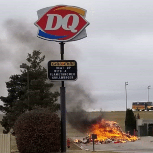 This happened in my hometown today. The contents of a trash truck caught fire and the driver dumped his load to save the truck in a Dairy Queen parking lot. The advertisement on the sign couldn't have been more perfect.: DQ  Grill&Chill  HEAT UP  WITH A  FLAMETHROWER  GRILLBURGER This happened in my hometown today. The contents of a trash truck caught fire and the driver dumped his load to save the truck in a Dairy Queen parking lot. The advertisement on the sign couldn't have been more perfect.