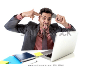 young attractive businessman sitting at office desk working stressed on computer laptop holding mobile phone against his forehead pointing hand in gun sign to his tempo overworked in work stress: ehutesst.ck  www.shutterstock.com 339155981 young attractive businessman sitting at office desk working stressed on computer laptop holding mobile phone against his forehead pointing hand in gun sign to his tempo overworked in work stress