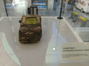 Nintendo, Saw, and Game: GAME BOY  DAMAGED IN GULF WAR  This Game Boy was damaged when barracks  were bombed during the 1990-1991 Gulf War  It still works! I visited Nintendo Mecca today and saw IT.