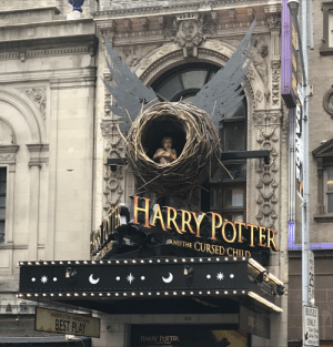 Creepy display on top of the entrance to Harry Potter and the Cursed Child in Times Square: HAR  RY POITER  ANDTHE CURSED CHILD  *  BUSES  ONLY  TAM-TDA  APH-7PH  MON THL  213  WINNER&TONY AR  BEST PLAY  HARRY POTTER  CL OmD Creepy display on top of the entrance to Harry Potter and the Cursed Child in Times Square