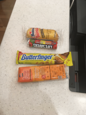 Candy, Life, and Protein: HARD CANDY  Butterfinger  CHERRY ORASPBERRY LTERVELON-ORANGE PENEAPPLE  S Ne Ar cial FaOS or Coces  Aded coiars fom rea 5oUrces  5 FLAVORS  TCANDIES  LIFE SAVERS  IARWATION  R CONTENT  crispety, crunchety, peanut-buttery!  NET WT 1907 (538)  BAR  rea  Toast  Chee  Sandwich Crackers  Cheddar  Cheese  Hostess  Twinkie  GOLDEN SPONGE CAKE  WITH CREAMY FILLING  PROTEIN  BEST BY: AUG13 2019  G 053021000 150  14:27 6  PAZ 7T I30  407E2  90TAT  BEST POd By How to survive a 12 hour flight