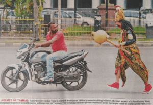 God, Police, and Traffic: HELMET OR YAMRAJ: An artiste dressed as Yamrai dord of death) runs behind a motorist riding without a helmet as part of a Road Safety Week  campaign organised by traffic police in Bangalore on Tuesday. The campaign aims to spread awareness about the importance of traffic safety rules. (AFP) So Indian Police had a guy dress up as God of Death to chase people not wearing helmets