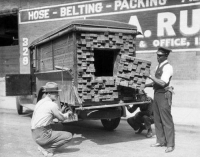 Alerted by the smell of a broken bottle of liquor, Federal agents inspect a lumber truck. 1926.: HOSE BELTING PACKINU  & OFFICE, Alerted by the smell of a broken bottle of liquor, Federal agents inspect a lumber truck. 1926.
