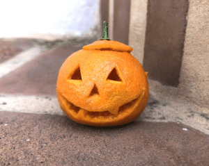 I carved a tiny clementine pumpkin. It's on my doorstep to ward off bad vibes.: I carved a tiny clementine pumpkin. It's on my doorstep to ward off bad vibes.