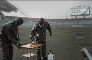 In Korea, cleaners sterilize 140 chairs 5 meters apart for job interviews on a soccer field.: In Korea, cleaners sterilize 140 chairs 5 meters apart for job interviews on a soccer field.