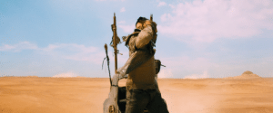 In Mad Max: Fury Road (2015), Max notices the Bullet Farmer as he is attempting to remove his jaw mask, prior to returning to the War Rig's cabin.: In Mad Max: Fury Road (2015), Max notices the Bullet Farmer as he is attempting to remove his jaw mask, prior to returning to the War Rig's cabin.