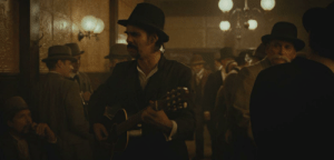 In The Assassination of Jesse James by the Coward Robert Ford, the man singing a song about Robert Ford's cowardice is Nick Cave one of the 2 composers for the film's soundtrack.: In The Assassination of Jesse James by the Coward Robert Ford, the man singing a song about Robert Ford's cowardice is Nick Cave one of the 2 composers for the film's soundtrack.