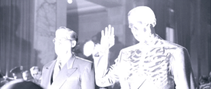 In The Aviator (2004) as Leonardo DiCaprio raises his right hand to swear during the Senate Hearings, Howard Hughes' skeleton is superimposed over him during a camera flash.: In The Aviator (2004) as Leonardo DiCaprio raises his right hand to swear during the Senate Hearings, Howard Hughes' skeleton is superimposed over him during a camera flash.