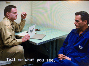 In the film The Master, an army shrink asks Arthur Fleck what he sees in the picture. This clearly a reference to his well known enemy that we all know about.: In the film The Master, an army shrink asks Arthur Fleck what he sees in the picture. This clearly a reference to his well known enemy that we all know about.